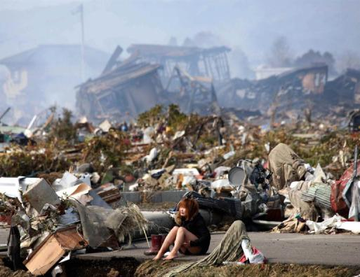 A woman sitting on a road cries amid the ruins of the city of Natori, Japan.